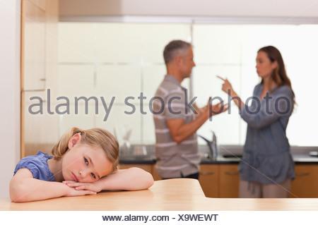 Sad little girl listening her parents having an argument - Stock Photo