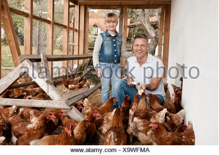Father and daughter in henhouse on organic farm - Stock Photo