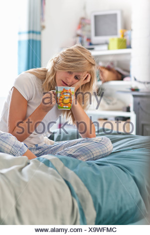 Woman with head in hands sitting on bed with coffee cup - Stock Photo