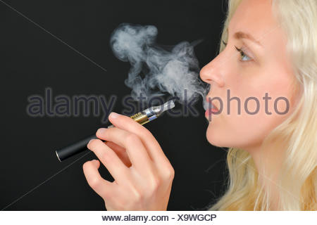 Woman trying an electronic cigarette - Stock Photo