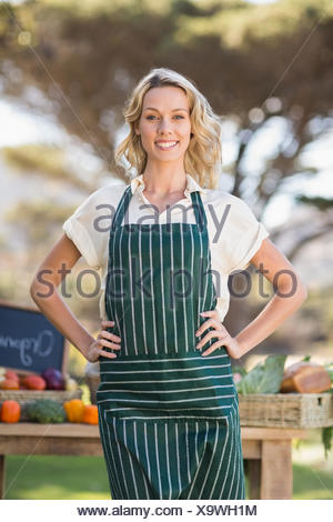 Smiling farmer woman with hands on hips - Stock Photo