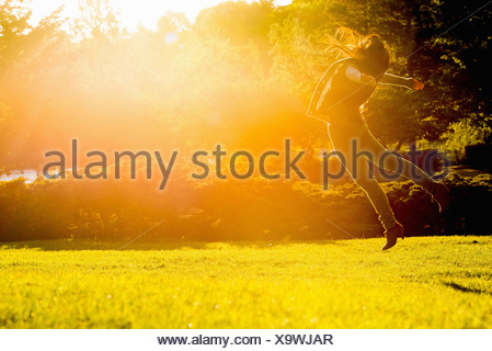Young female jumping mid air in park - Stock Photo