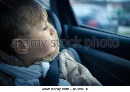 Close-up of young boy in car seat - Stock Photo