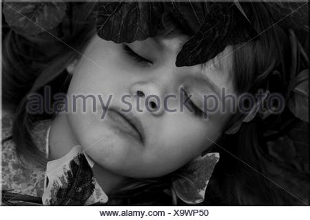 Overhead view of a girl lying on grass sleeping - Stock Photo