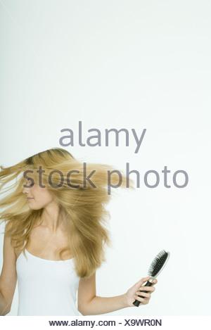 Teenage girl holding brush and swinging hair - Stock Photo