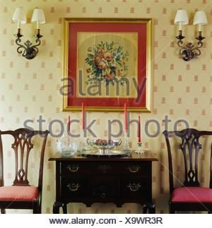 ... Wall Lights On Either Side Of Framed Floral Tapestry Above Antique Table  And Chairs In