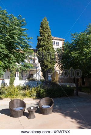 Warm courtyard with table and chairs in Spain - Stock Photo