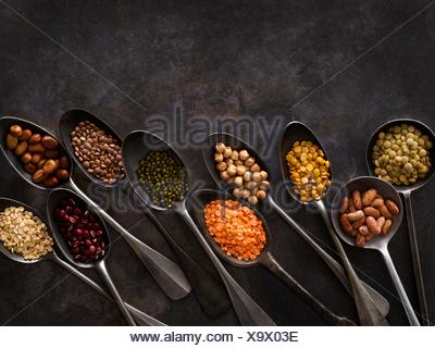 Pulses on metal spoons, overhead view. - Stock Photo