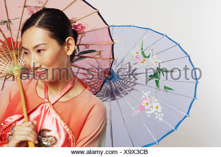 Close-up of a mid adult woman holding two umbrellas and smiling - Stock Photo