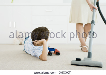Boy lying on the ground with toys, looking up at his mother vacuuming around him - Stock Photo