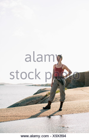 Full length of woman in sports clothing standing on rock at seaside - Stock Photo