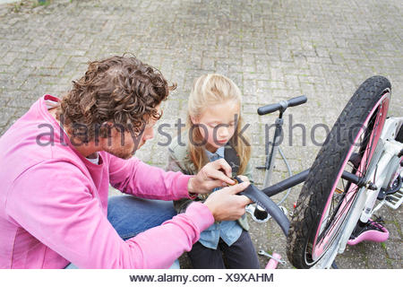 Father and daughter mending bike - Stock Photo