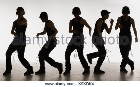 composite image of a boy dancing with headphones - Stock Photo