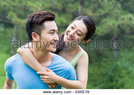 Young man giving her girlfriend a piggy back ride - Stock Photo