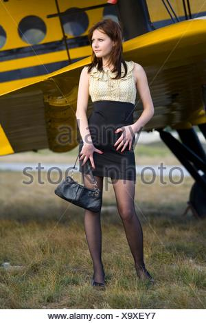 Fanciful young woman is standing besides Yellow biplane airplane - Stock Photo