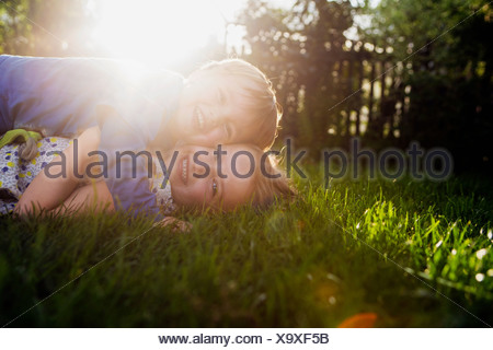 Brother and sister lying on grass, hugging - Stock Photo