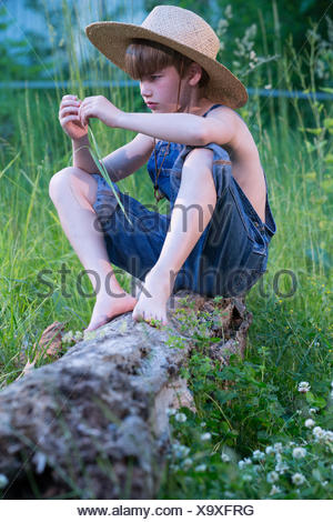 Young Boy Wearing Overalls Sitting On Tree Wearing Straw Hat Stock