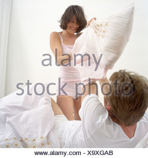 Happy couple in pillow fight - Stock Photo