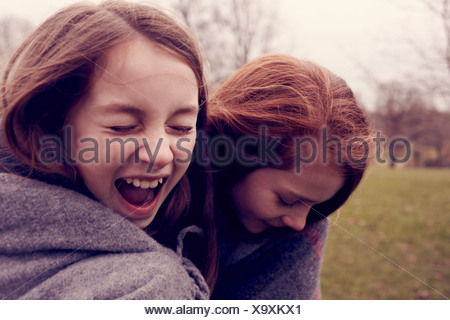 Young friends wrapped in a blanket and laughing outdoors - Stock Photo