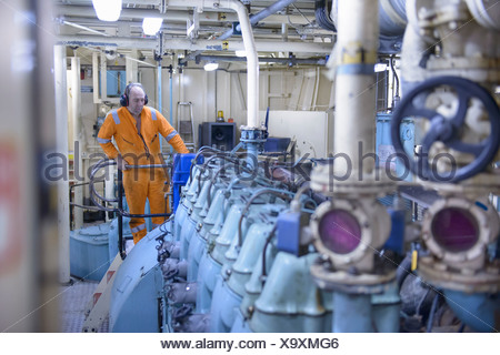 Engineer standing in engine room - Stock Photo