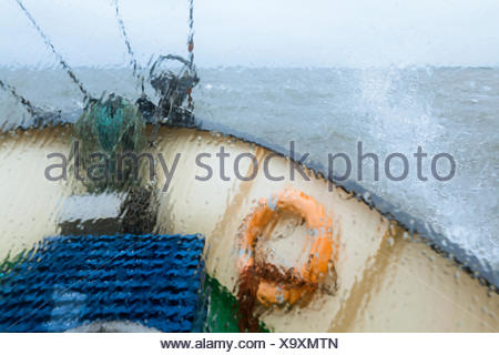 View through the wet window of the bow of the shrimp boat 'Columbus' from Pellworm island, travelling in North Frisian coastal - Stock Photo