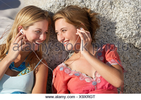 Two teenage girls 17 19 listening to MP3 player on rocky beach sharing headphones smiling - Stock Photo