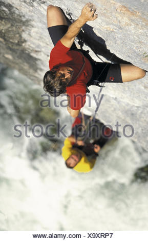two climbers on steep rock face - Stock Photo