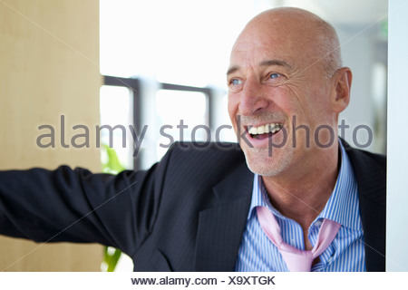 Laughing businessman in loose tie - Stock Photo