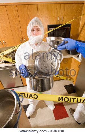 Man wearing coveralls and holding pots in dirty kitchen - Stock Photo