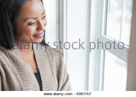 Smiling woman looking out window at home - Stock Photo