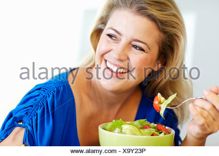 Smiling woman eating salad at table - Stock Photo