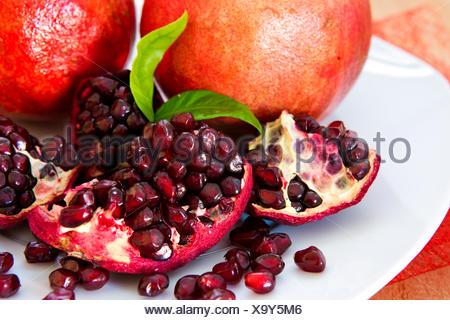 Juicy pomegranates on wood. - Stock Photo