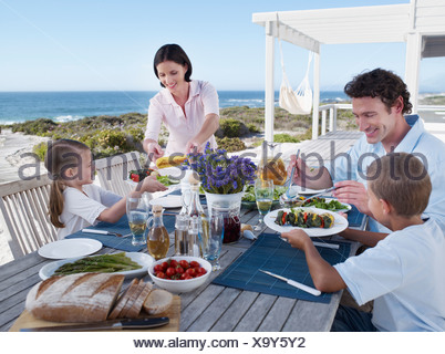 Family enjoying a meal outdoors on their terrace - Stock Photo