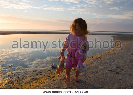 Baby girl carrying dolls on the beach - Stock Photo