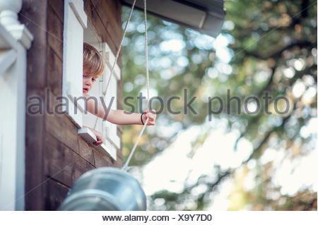 Boy pulling a bucket up to his treehouse - Stock Photo