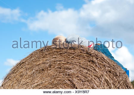 Boy lying on hay bale - Stock Photo