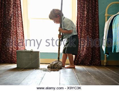 Toddler in school uniform cleaning floor - Stock Photo