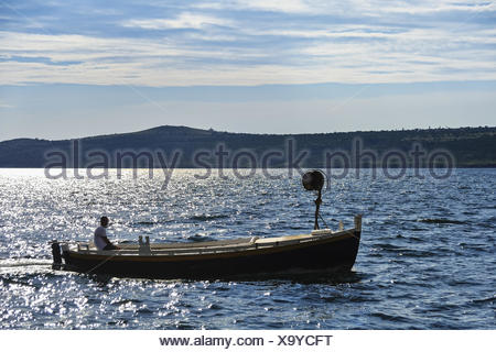 Fisherman in boat travels across the sea - Stock Photo