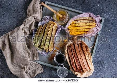 Variety of sliced american ombre chocolate, green tea matcha and turmeric pancakes served in paper paper wrapper with honey sauces on wood tray over b - Stock Photo