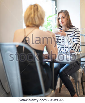 Young female friends having coffee at cafe - Stock Photo