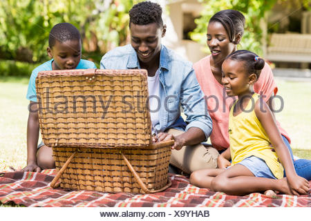 Happy family looking the wicker basket - Stock Photo