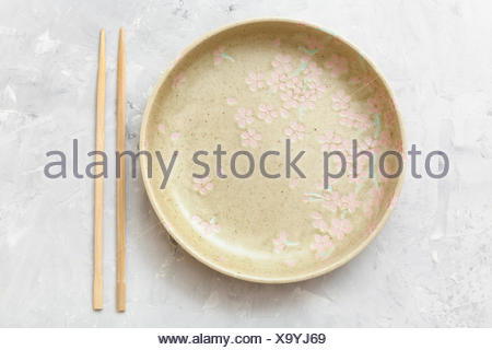 above view yellow plate and chopsticks on concrete - Stock Photo