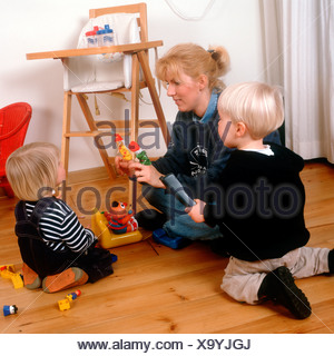 Child care worker or single mother playing puppetry with finger puppets with children in her home, SerieCVS100012034 - Stock Photo