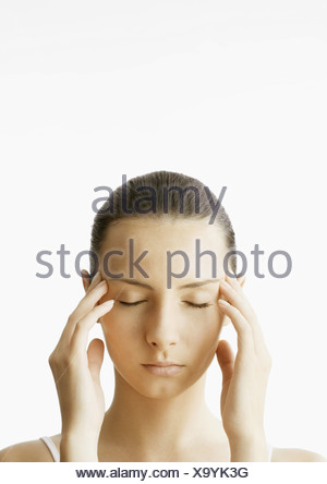 Woman with fingers on temples - Stock Photo