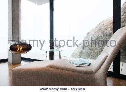 Chair and fireplace in modern living room - Stock Photo