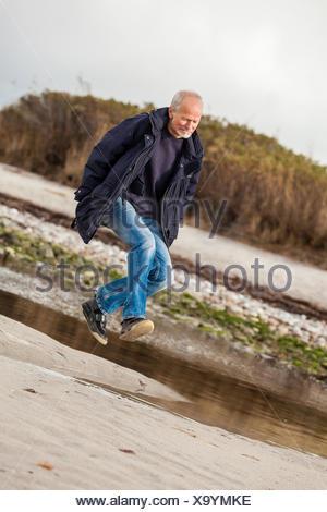 lachender glücklicher aktiver rentner senior älterer mann im herbst im freien - Stock Photo
