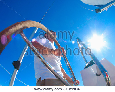 A skipper steering on board a yacht under blue skies while cruising in Pittwater on the North Shore from Sydney, Australia. - Stock Photo