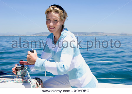 Woman winding rope pulley of boat rigging on deck of sailing boat out at sea, smiling, side view, portrait - Stock Photo