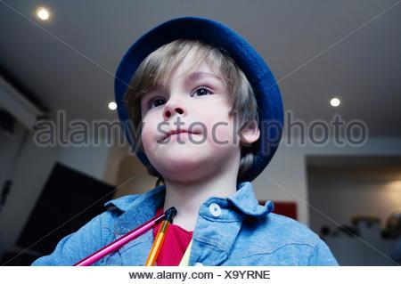 Low Angle View Of Cute Boy With Pencil In House - Stock Photo