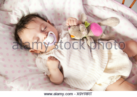 Baby girl sleeping in wicker crib with toy - Stock Photo